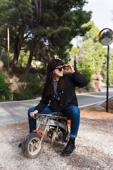Happy woman sitting on small motorcycle
