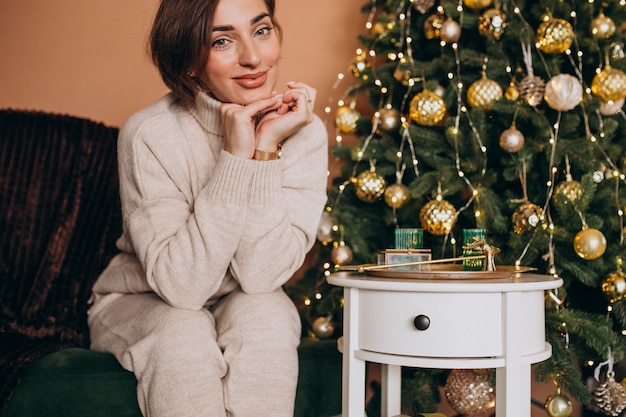 Happy woman sitting on sofa by the christmas tree