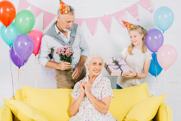 Happy woman sitting on sofa in front of husband and granddaughter holding birthday gifts