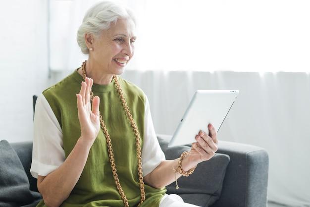 Happy woman sitting on sofa saying goodbye on digital tablet
