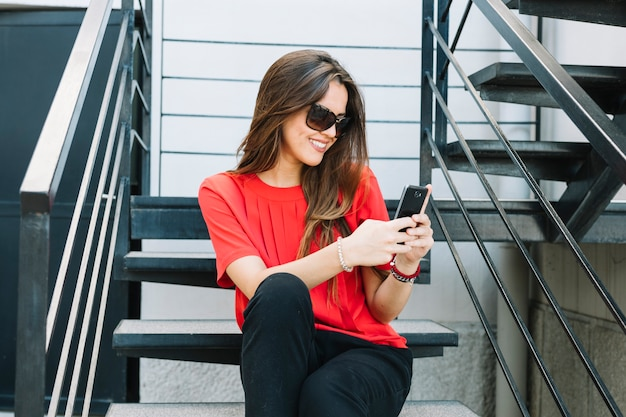 Happy woman sitting on staircase using mobile phone
