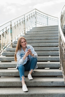 Happy woman sitting on staircases and using smartphone