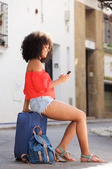 Happy woman sitting on suitcase with mobile phone