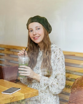 Happy woman sitting at table holding smoothie