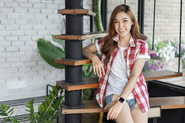 Happy woman sitting on wooden stair