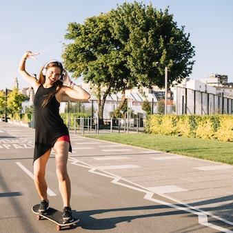 Happy woman skateboarding on street