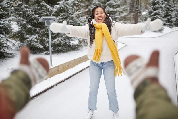Счастливая женщина на коньках на катке со своим парнем, который ее ловит