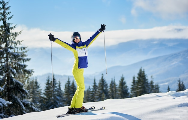 Счастливая женщина-лыжник позирует на лыжах