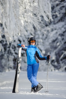 Happy woman skier on a ski slope in the forest