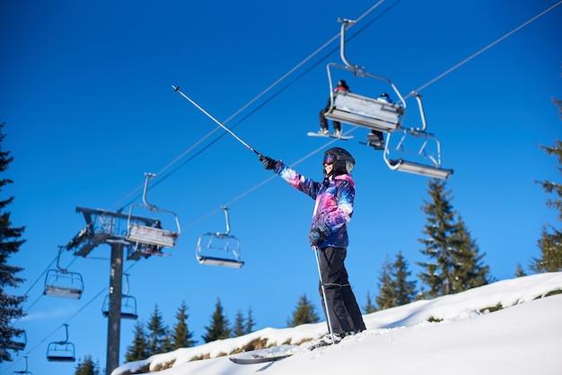 雪に覆われた山の斜面のスキーリフトの近くに立っている幸せな女性スキーヤー。冬休みの晴れた日。一般的な見解。
