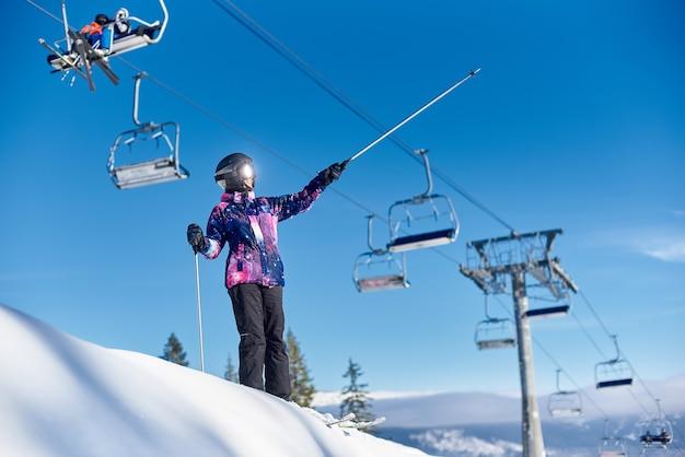 Счастливый лыжник женщины, стоящий возле подъемника на заснеженном склоне горы. солнечный день во время зимних каникул. общий вид.