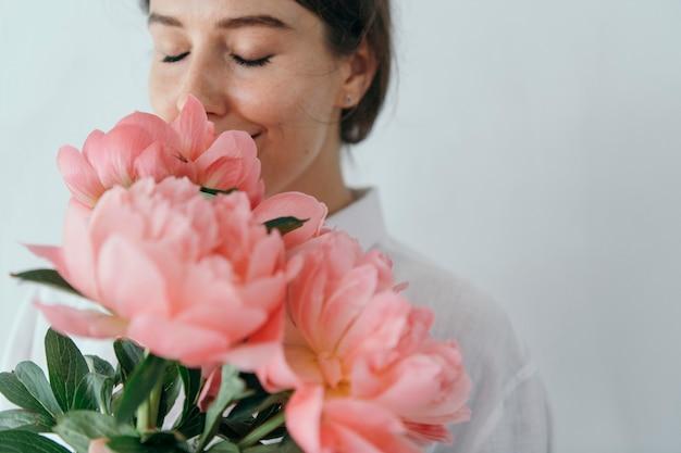 珊瑚の夕日の牡丹の花束をかぐ幸せな女性