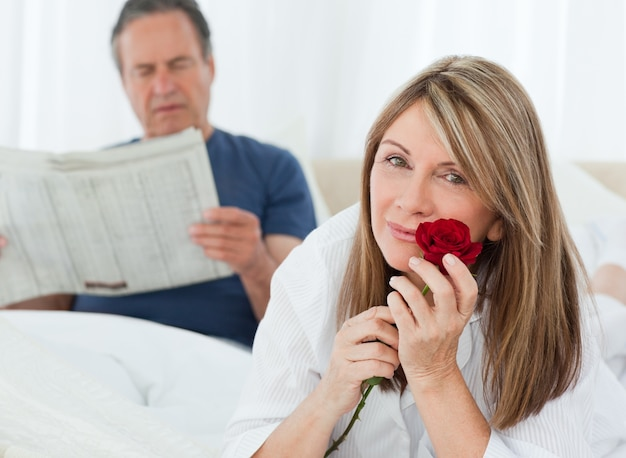 Happy woman smelling her rose while her husband is reading a newspaper