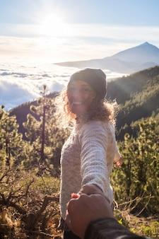 幸せな女性は笑顔で、山で彼氏と一緒に屋外で楽しんでください-手をつないで、旅行休暇や週末の時間を楽しんでいるカップルを愛するハメ撮り Premium写真