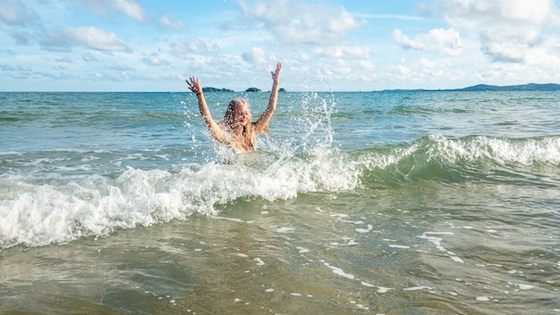 笑顔でビーチで楽しんで幸せな女。帽子とビーチを走る美しい少女の夏の肖像画。笑っている女の子