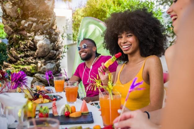Счастливая женщина улыбается и весело с друзьями на открытом воздухе на летней вечеринке