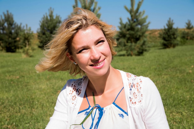 Счастливая женщина улыбается и смотрит в камеру в солнечный летний день