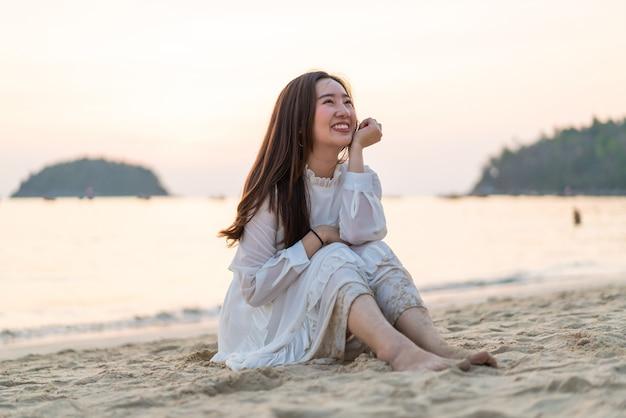 Счастливая женщина, улыбаясь на берегу моря