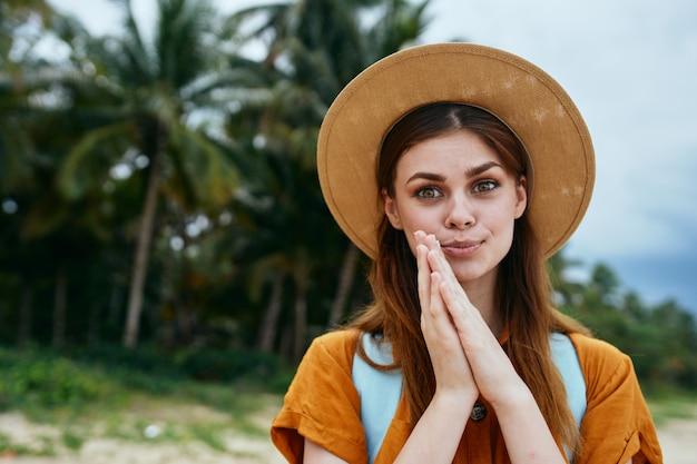 Счастливая женщина улыбается на острове и смотрит в камеру