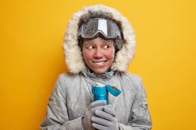 Happy woman snowboarder coverd with hoarfrost tries to warm during freezing day with hot beverage dressed in winter clothes has journey in northern pole holds thermos of tea. extreme seasonal sport