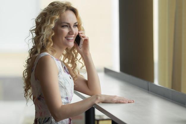 아침 식사 시간에 커피숍에 앉아 휴대전화로 말하는 행복한 여성.