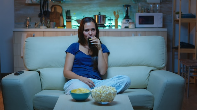 Happy woman spending her free time watching tv eating popcorn and drinking juice. excited amused home alone lady enjoying the evening at home sitting on comfortable couch dressed in pajamas.