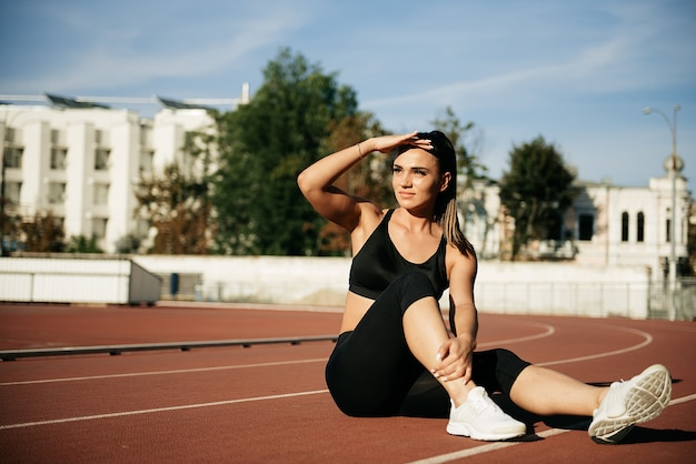 Happy woman in sportswear sitting on the redcoated stadium track outdoors