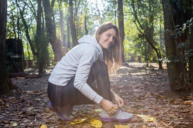 Happy woman in sportswear tying shoelaces
