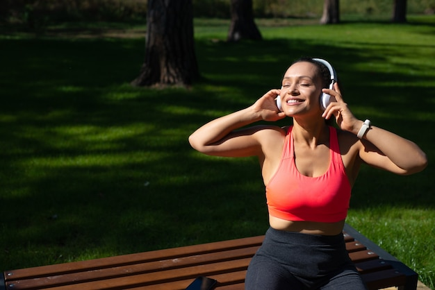 Happy woman in sportswear with headphones enjoying listening music while relawing in the park