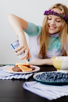 Happy woman squeezing whip cream over her waffles