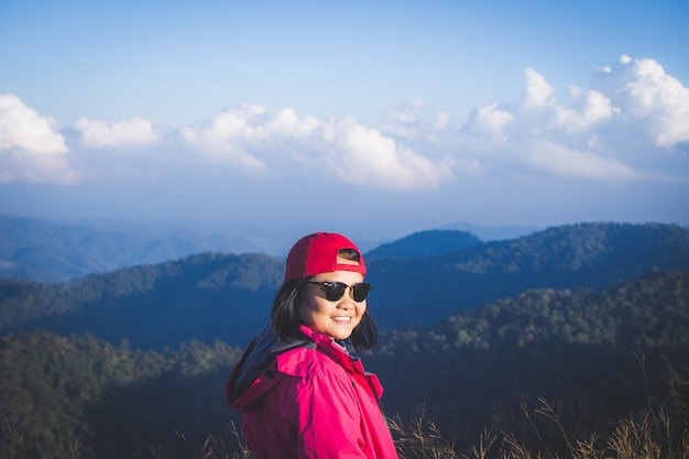 Happy woman stand on top mountain looking view with mist and cloud.