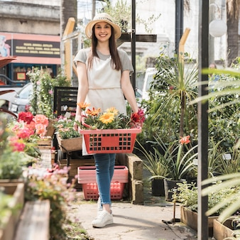 Happy woman standing in greenhouse with container of fresh flowers