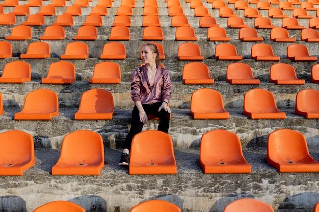 Счастливая женщина, стоящая среди рядов пустых мест на стадионе, аплодирующая с поднятыми руками, пробивая воздух