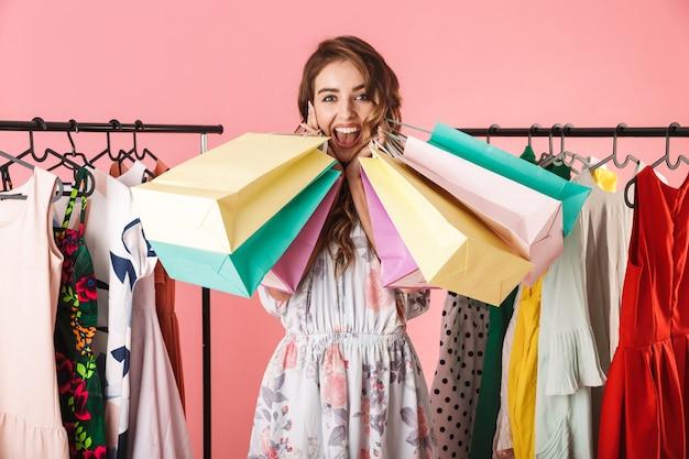Счастливая женщина стоит в магазине возле вешалки и держит красочные сумки, изолированные на розовом