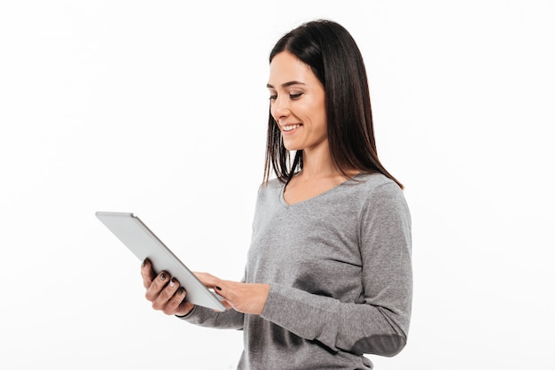Happy woman standing isolated using tablet computer.