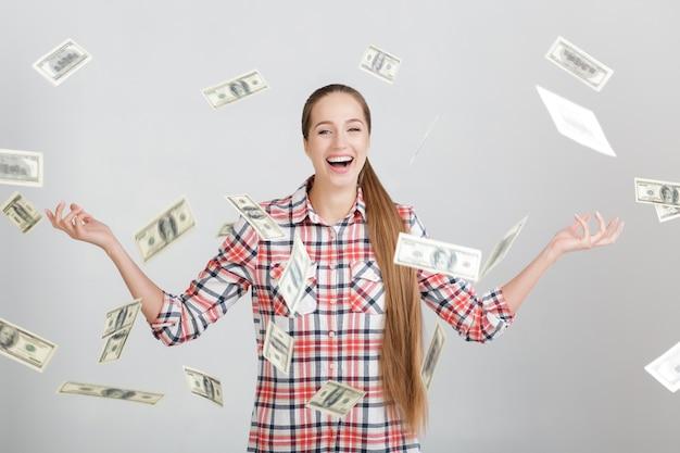 Happy woman standing under money rain