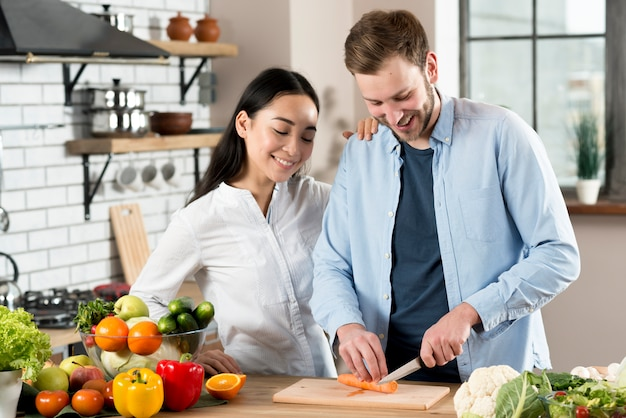 Happy woman standing near her husband slicing carrot on wooden chopping board