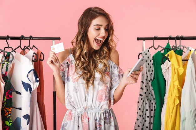 Happy woman standing near wardrobe while holding smartphone and credit card isolated on pink