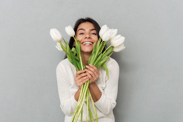花と灰色の壁の上に立って幸せな女