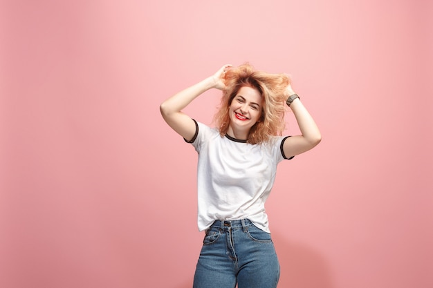 The happy woman standing and smiling against pink wall.