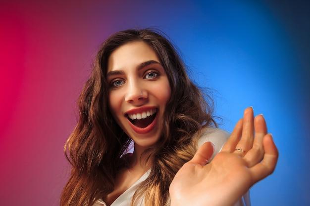 立っている幸せな女性、色付きのスタジオの背景に笑みを浮かべて。美しい女性の半身像。若いは女性を満足させます。人間の感情、表情の概念。