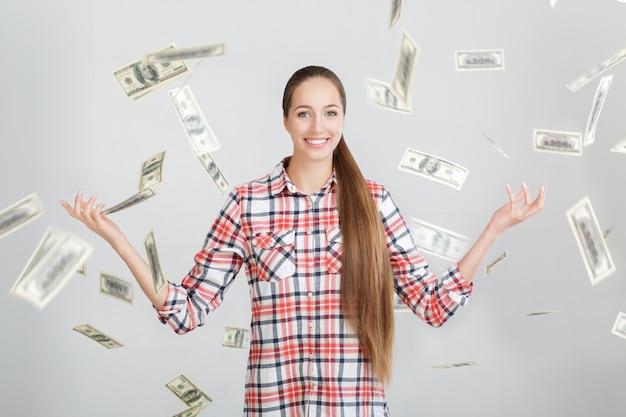 お金の雨の下に立っている幸せな女性