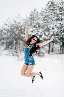 Happy woman standing in winter forest