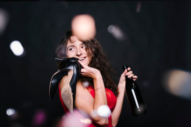 Happy woman standing with bottle on party