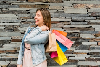 Happy woman standing with colourful shopping bags
