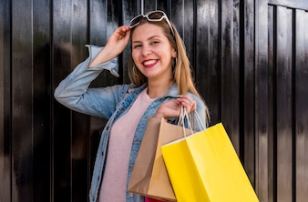 Happy woman standing with shopping bags at dark wall