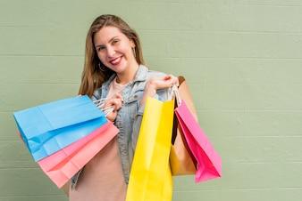 壁に買い物袋を持って立っている幸せな女