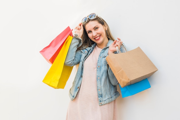 Happy woman standing with shopping bags at light wall