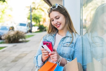 Happy woman standing with shopping bags, smartphone and credit card outside