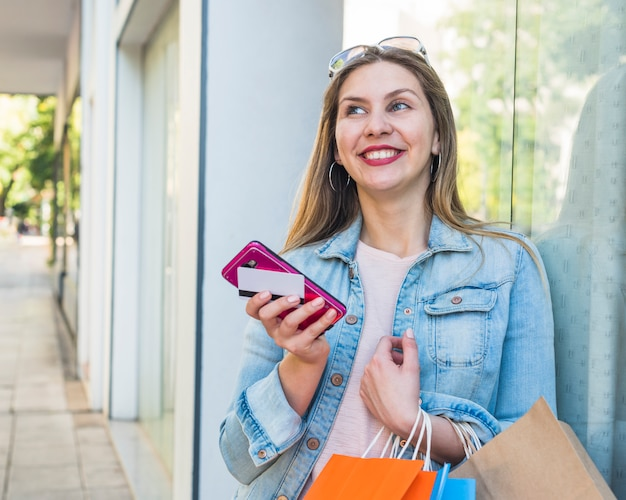 Happy woman standing with shopping bags, smartphone and credit card